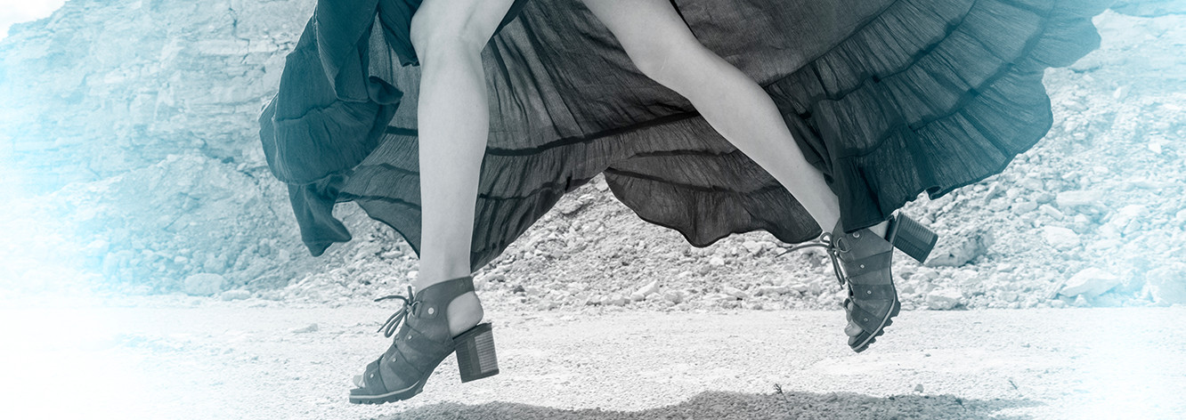 A woman in SOREL Addington Lace sandals in the desert.