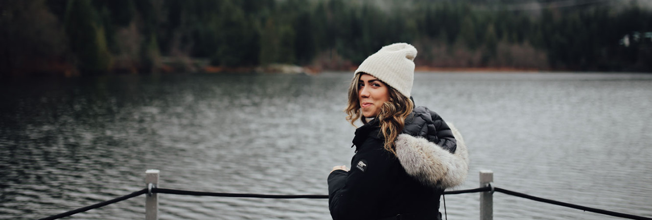 Woman by a snowy lake wearing a parka and snow boots.