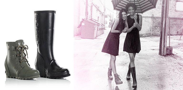 Two rain boots, one green, one black, and two women under an umbrella on the street.