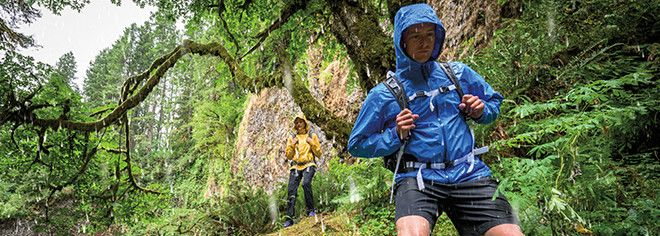 A man in a raincoat hiking  in the forest, video prompt.