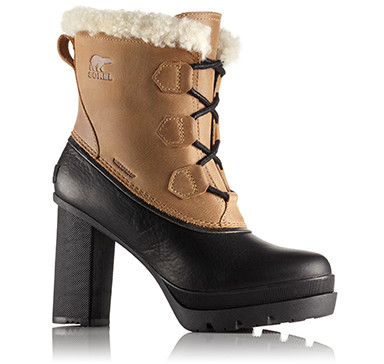Tan and black heeled leather boot with shearling cuff on white background.