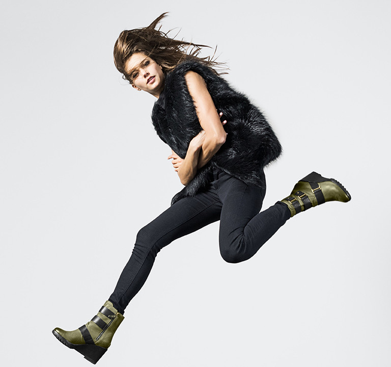 A woman jumping in green wedge boots.
