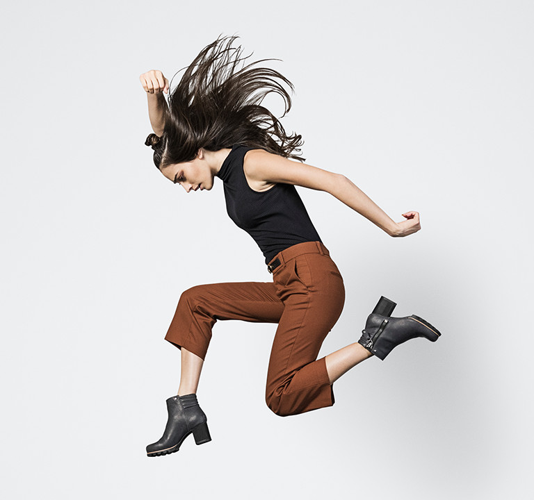 A woman jumping in ankle boots with heels.
