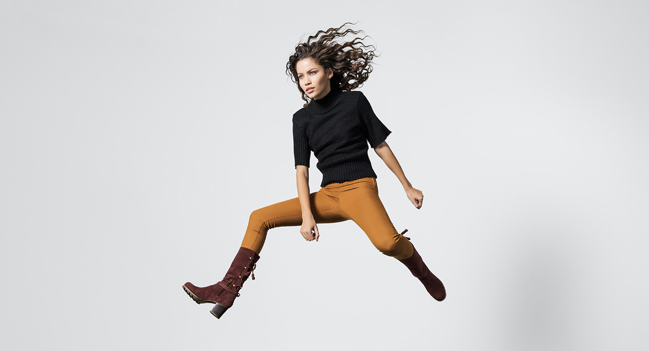 A woman jumping in brown mid-calf boots.