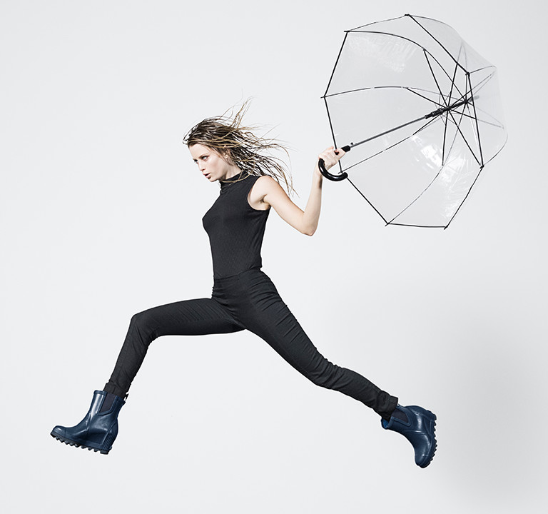 A woman jumping in rain boots and an umbrella.