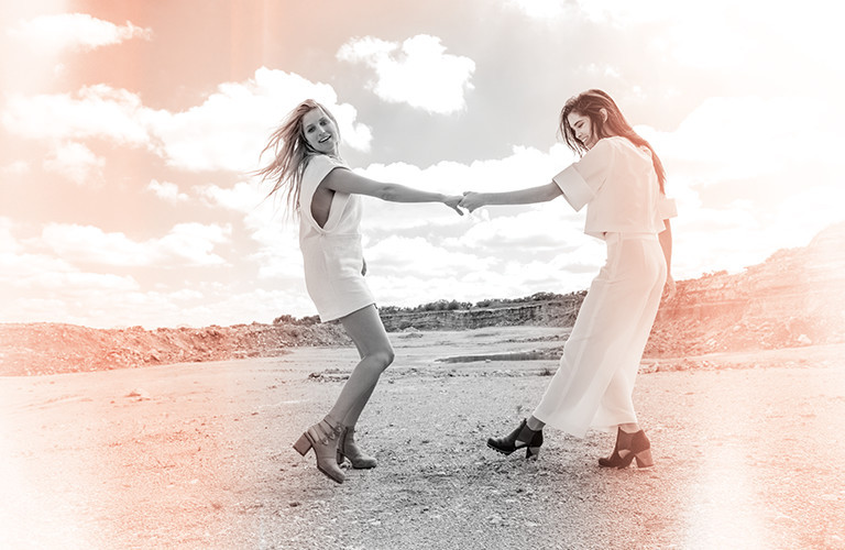 Two young women holding hands in the desert.