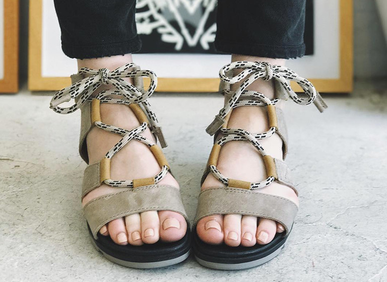 A woman's feet in  leather sandals.