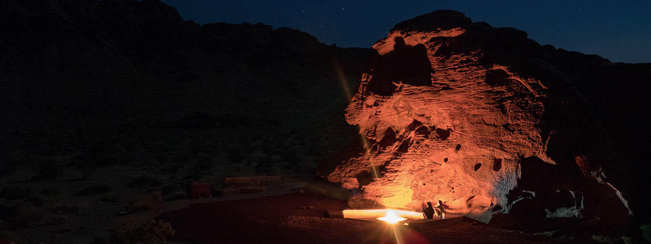 Faith and Mark sit beside a campfire, the glow of which illuminates large red rock formations all around them.