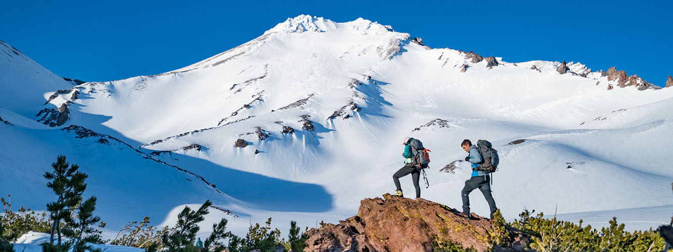 Video of Mt. Shasta journey; Image of Faith and Mark climbing a rock near the treeline and looking up at Mt. Shasta towering up in front of them.
