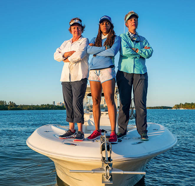 Faith and her team stand on the bow of the Ladyfish.
