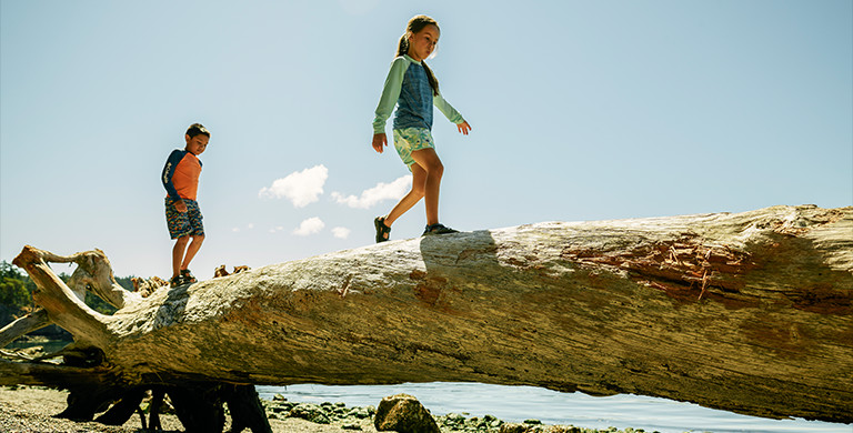 Two children walk on a log at the beach.