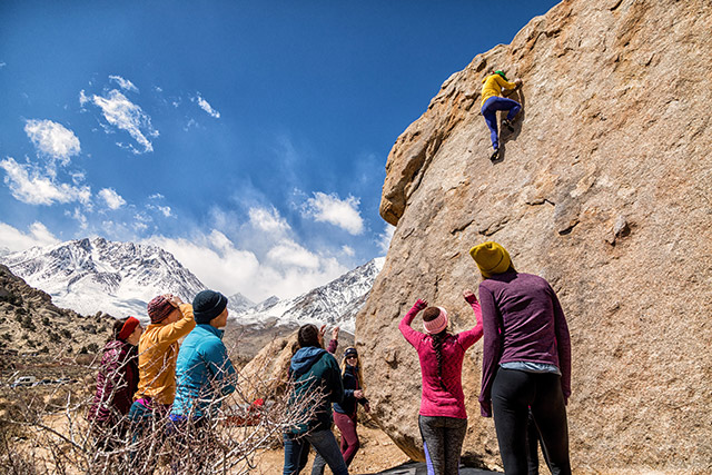 A group of people watch as a climber maneuvers up a boulder.