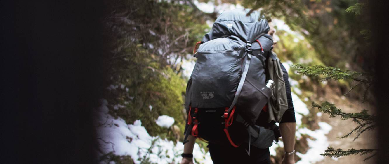 A man wearing a Mountain Hardwear backpack walks up a forested mountain trail.