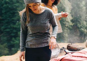 A woman wearing a lightweight base layer stands near a campsite.