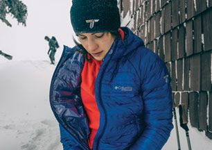A woman zips up an insulated mid-layer jacket.