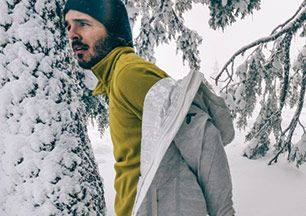 A man wearing a mid-layer in the snowy woods.