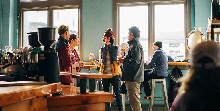 Four young people in outdoor casual wear stand and talk in a coffee shop.