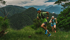 A man and woman in Columbia Montrail gear run up a mountain trail.