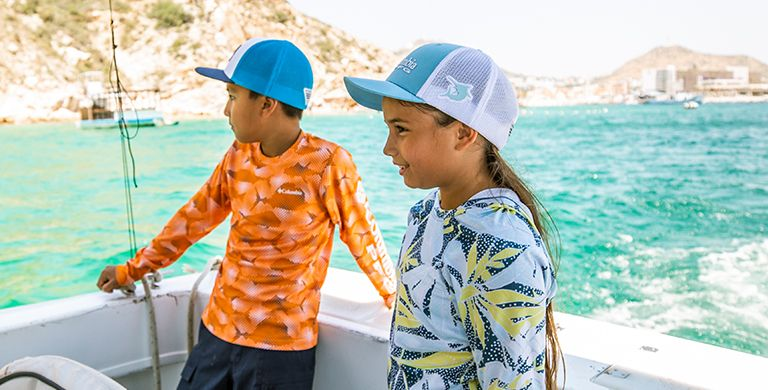 Two kids fishing on a boat in the ocean.