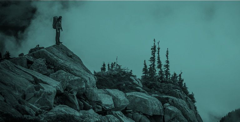 A lone backpacker stands atop a rocky crag.