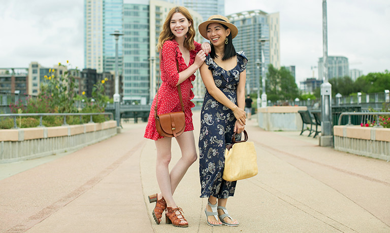 An image of two stylish women standing in the street wearing sandals.