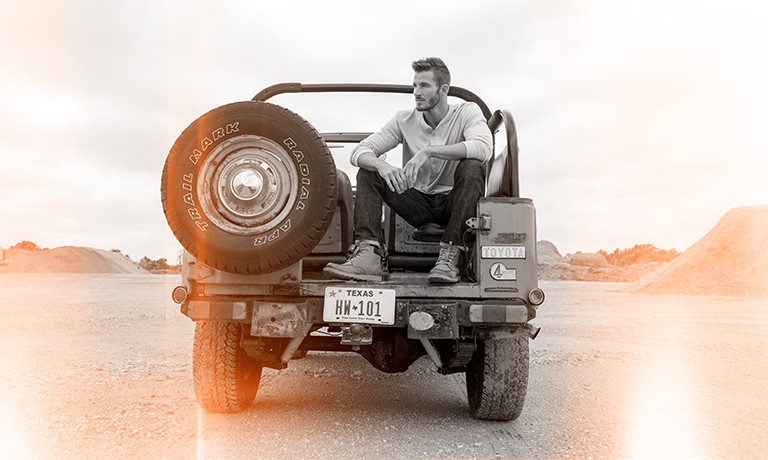 An image of a man wearing lace up boots sitting in the back of a truck.