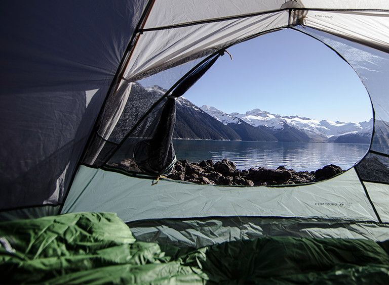 A Lamina Z sleeping bag inside a tent with a lake and mountain setting in the background.
