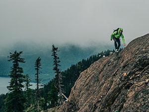 A man in Columbia gear climbing a mountain ridge.