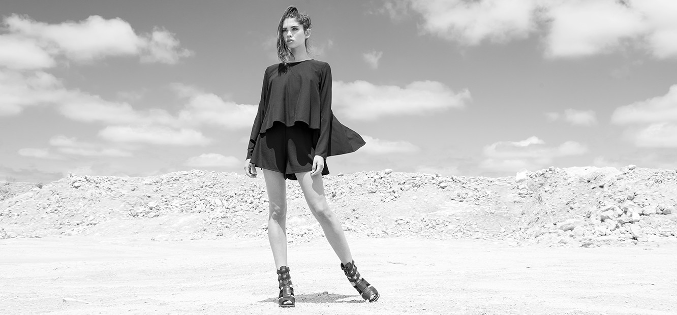A young woman in the desert in shorts and gladiator sandals.