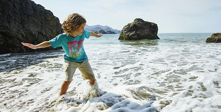A child wearing Columbia sportswear pretends to surf in an ankle-deep ocean shore.