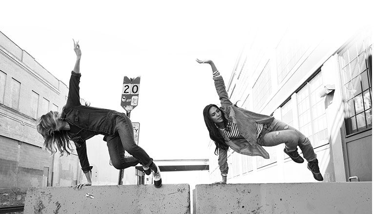 two women jumping over a concrete barrier in Sorel boots