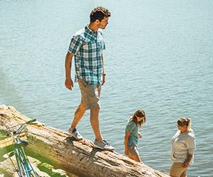 A man in Columbia gear walking on a log beside a river