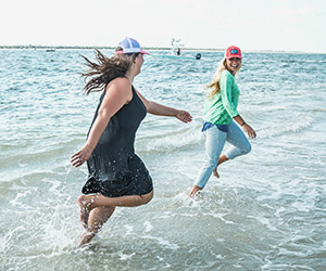 Two women in Columbia dresses at the beach