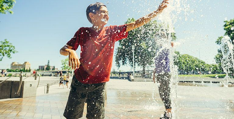 A boy in Columbia gear playing in a water fountain