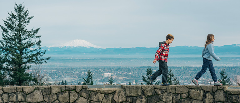 Two children walk on a rock ledge with mountains in the background.