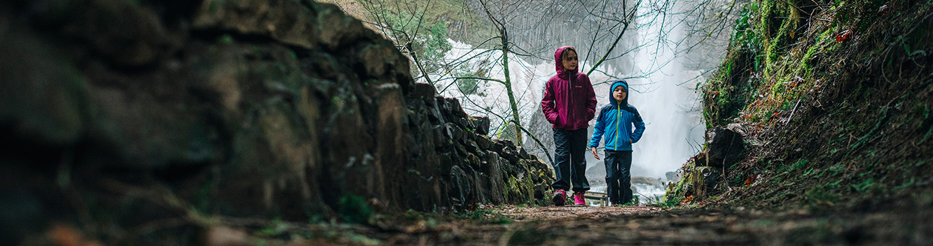 A boy and a girl walk on a wet trail with a waterfall in the background.