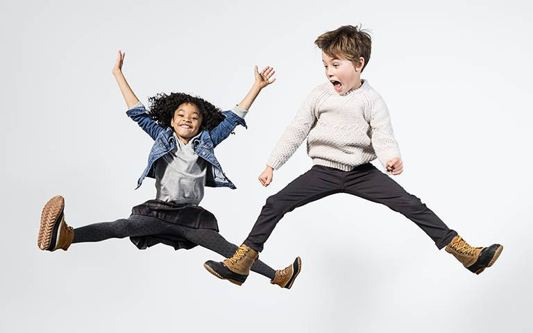 A girl and boy jumping through the air in boots.