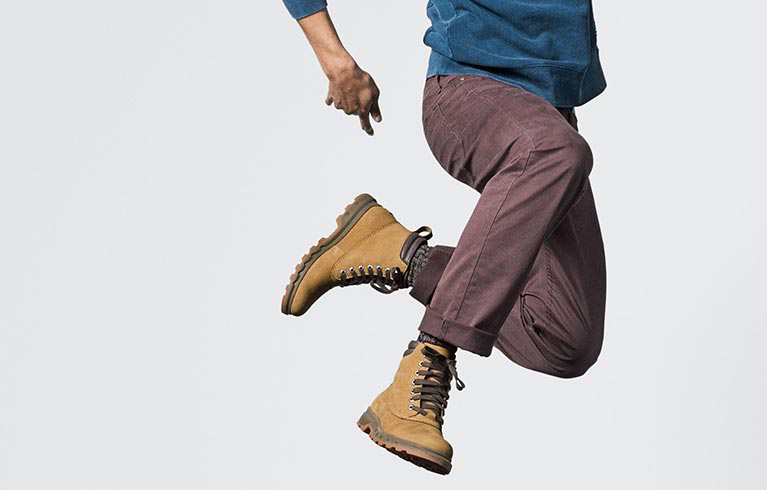 A young man jumping in tan and brown Portzman Lace boots.