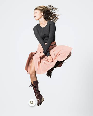 A woman jumping in a skirt and lace-up boots.