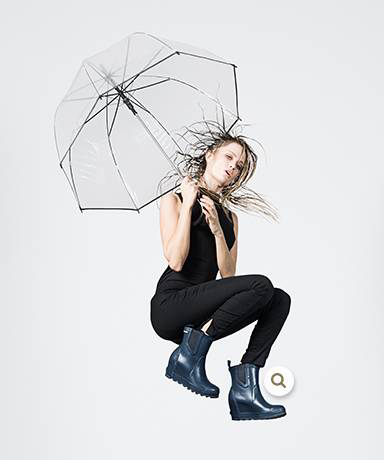 A woman jumping with an umbrella and ankle boots.