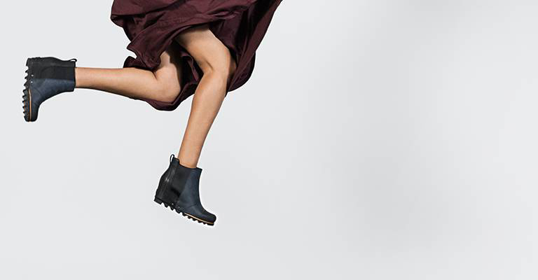A woman jumping in wedge ankle boots.