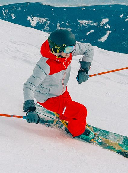 A woman in a red and grey outfit skiing