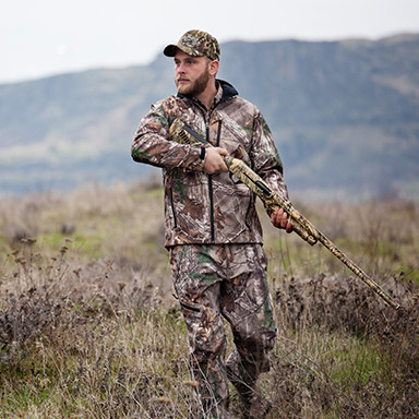 A man in camouflaged gear hunting in a field.