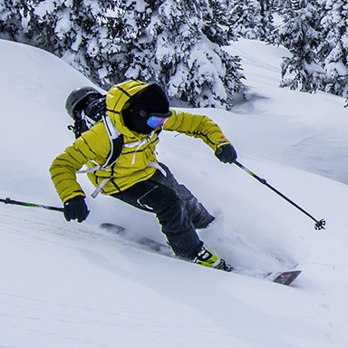 A skier making a turn in fresh snow on a mountain.