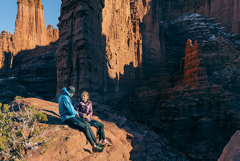 A man and a woman hiking in a canyon.