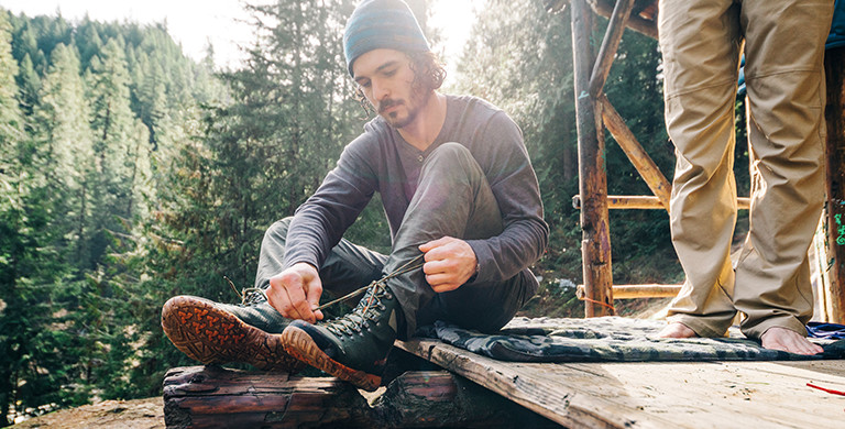 A man lacing up his hiking boots in a forest setting.