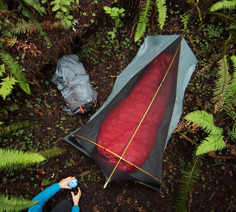 Man in woods with tent, sleeping and backpack.