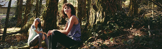 Two women sitting on logs in the woods.
