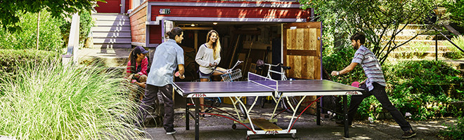 Two men playing ping pong outside a house.