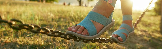 A cropped in image of a woman wearing sandals in a park.